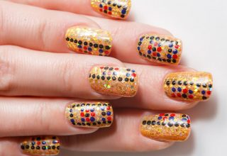 Red and black dotted design on gold basecoat.