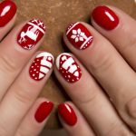 Christmas nails of white reindeer and trees on red base coat.