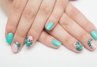 Ring finger nails adorned with a butterfly on each.