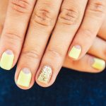 Yellow nails with a gold ring fingernail.