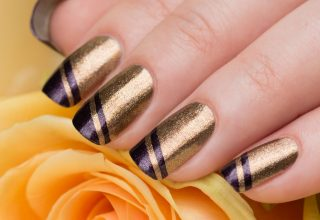 Gold nails with purple stripes.